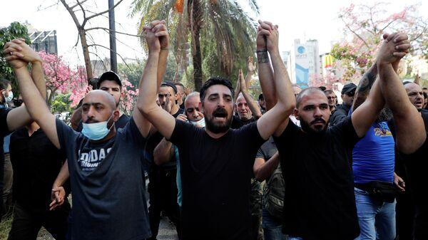 Сторонники шиитских группировок Хезболла и Амаль выкрикивают лозунги против судьи Тарека Битара
