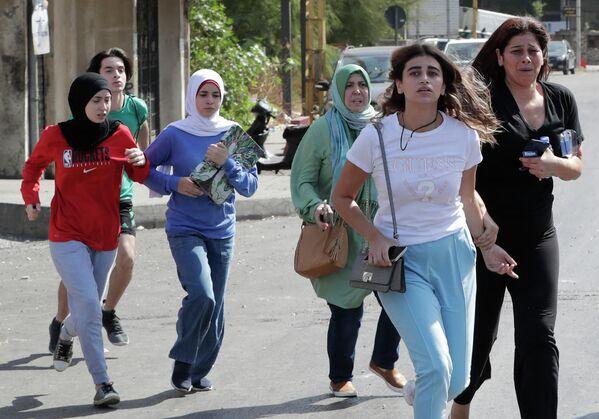 Мирные жители спасаются бегством во время столкновений в районе Тайунех, в южном пригороде столицы Бейрута, после демонстрации сторонников Хезболлы и движения Амаль.