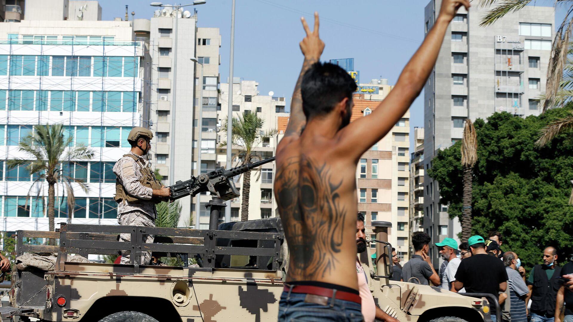 Участник акции протеста на фоне военных в южном пригороде Бейрута Дахие, Ливан - РИА Новости, 1920, 14.10.2021