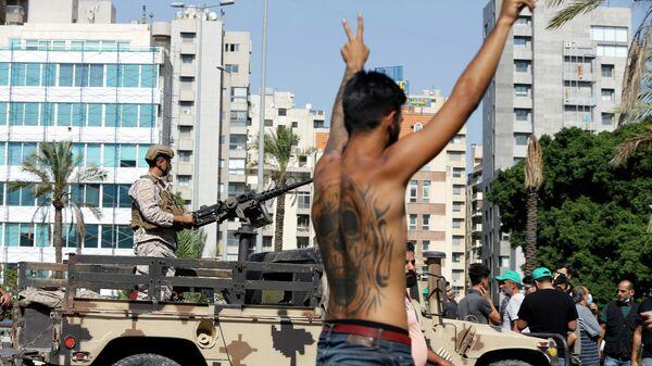 Участник акции протеста на фоне военных в южном пригороде Бейрута Дахие, Ливан