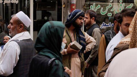 Люди на рынке обмена валюты в Кабуле