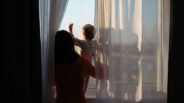 Мать с ребенком возле окна