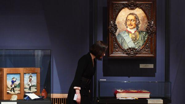 Посетительница выставки Янтарная комната и другие проекты. Тайны реставрации у картины из янтаря Петра I