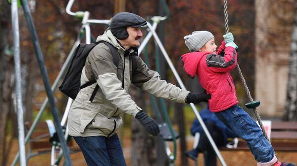 Мужчина с ребенком на детской площадке в День отца