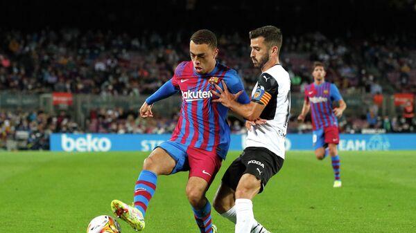 Защитник Барселоны Сержиньо Дест (слева) и защитник Валенсии Хосе Гайя