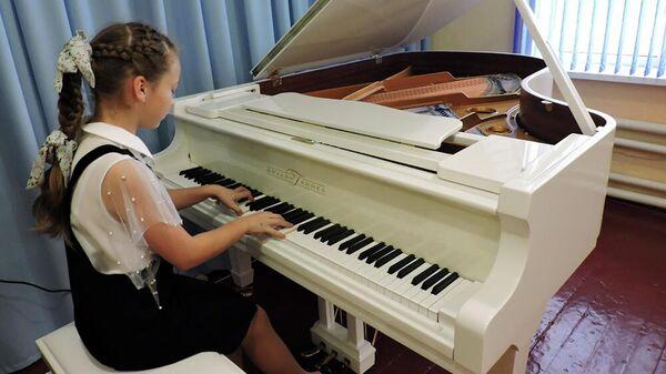 Девочка играет на белом рояле