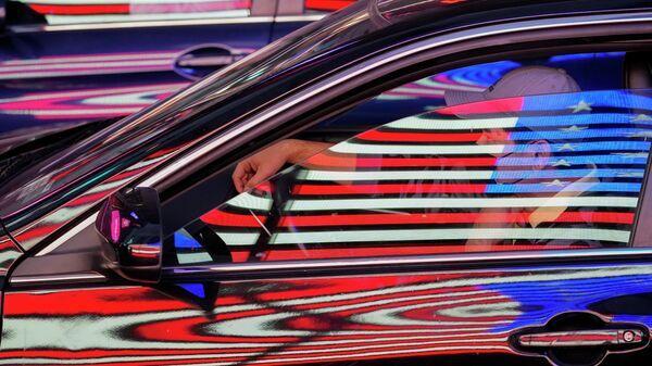 Флаг США отражается на автомобилях на Таймс-сквер в Нью-Йорке
