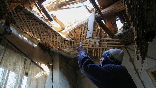 42-летний житель Донецка демонстрирует состояние своего дома на улице Дружбы, в крышу которого попал снаряд