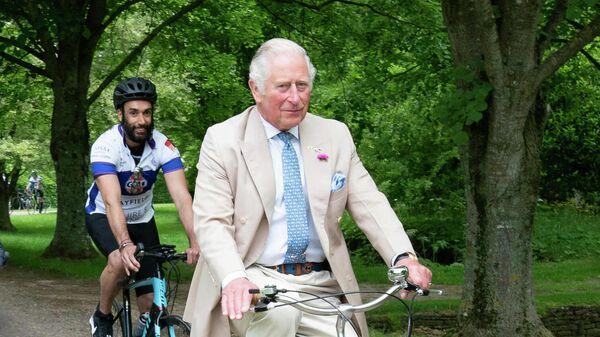 Британский принц Чарльз едет на велосипеде в Глостершире