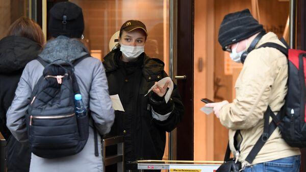 Посетители получают заказы навынос на улице у Макдоналдса в Казани, в котором закрыты залы