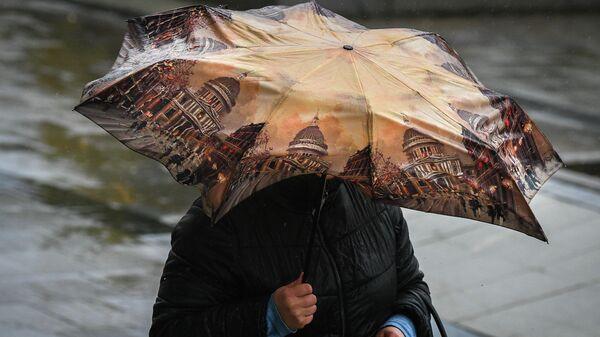 Женщина идет под зонтом во время дождя в Москве
