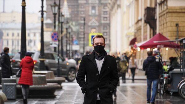 Молодой человек в защитной маске на набережной канала Грибоедова в Санкт-Петербурге