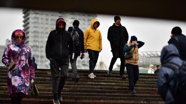 Люди спускаются в подземный переход на одной из улиц в Москве