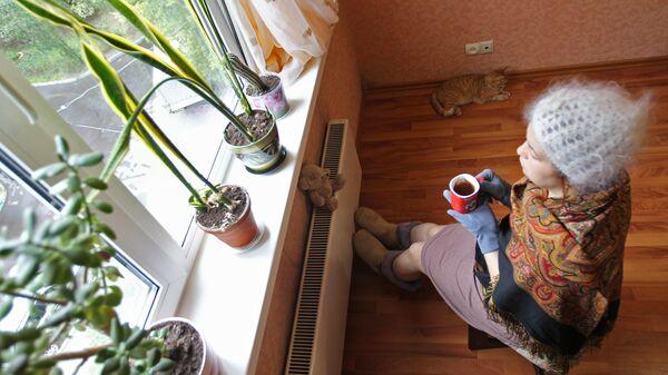 Жительница Москвы сидит в теплой одежде у батареи в квартире