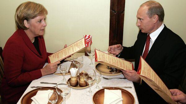 Ангела Меркель и президент России Владимир Путин во время ужина в ресторане - трактире Вечный зов в Томске.