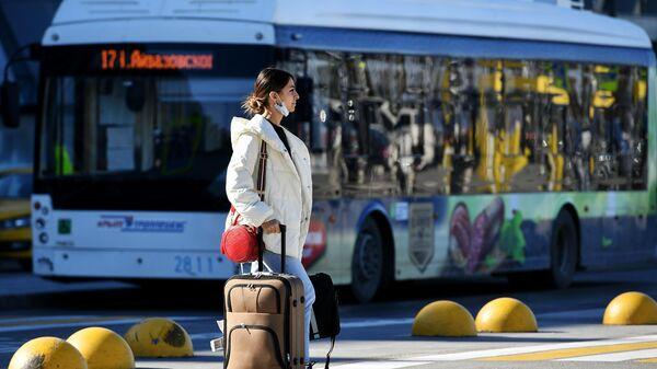 Девушка на автомобильной стоянке возле здания международного аэропорта Симферополь имени И. К. Айвазовского