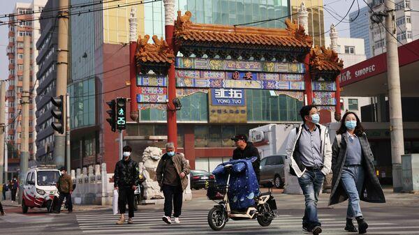 Люди в защитных масках на улицах Пекина
