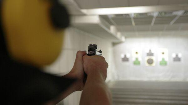 Спортсмен стреляет по мишеням из пистолета