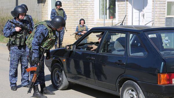 Сотрудники полиции досматривают автомобиль на месте проведения контртеррористической операции. Архивное фото