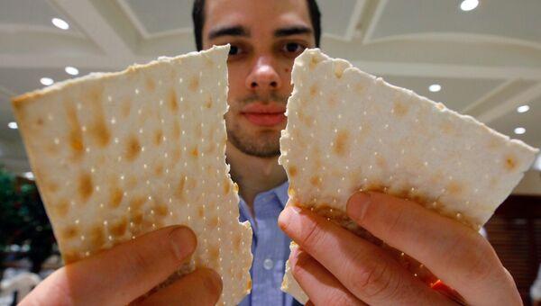 Преломление мацы (пресного хлеба) во время Седра (пасхального ужина), посвященного первому дню праздника Песах, архивное фото