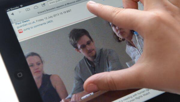 Журналист смотрит на экран компьютера, на котором открыта фотография экс-сотрудника ЦРУ Эдварда Сноудена. Архивное фото.