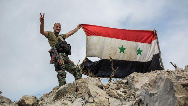 Военнослужащий правительственной армии Сирии с флагом страны на позиции войск на одной из вершин возле города Кесаб