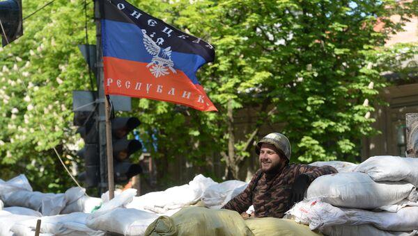 Активист сил самообороны сторонников федерализации Украины на баррикаде под флагом ДНР. Архивное фото