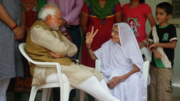 Нарендра Моди со своей матерью, которая показывает знак победы после объявления предварительных результатов выборов в Индии