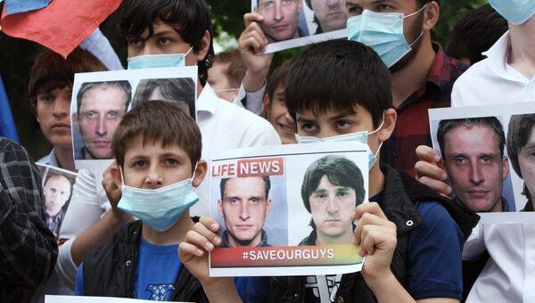Активисты держат фото Олега Сидякина и Марата Сайченко во время акции в поддержку задержанных на Украине российских журналистов. Архивное фото