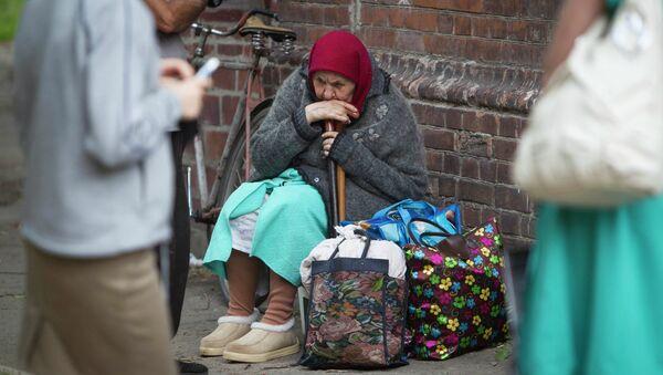 Женщина сидит на земле в ожидании автобуса, чтобы покинуть город Славянск