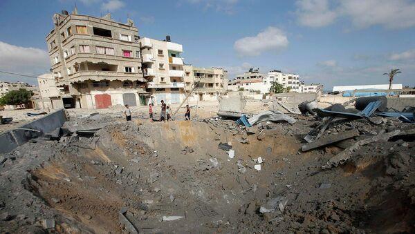Палестинцы рядом с кратером образовавшемся в результате удара с воздуха Израильской армией