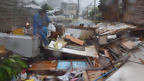 Житель пробирается через разрушения тайфуном Ногури, префектура Окинава, Япония