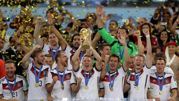 Футболист Бастиан Швайнштайгер держит кубок ФИФА после футбольного матча между Германией и Аргентиной на стадионе Маракана в Рио-де-Жанейро