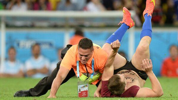 Стюард задерживает болельщика, выбежавшего на поле в финальном матче чемпионата мира по футболу