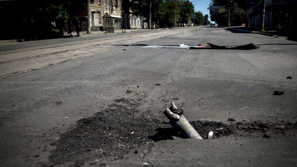 Фрагмент снаряда, застрявший в асфальте после артобстрела украинскими силовиками. Архивное фото