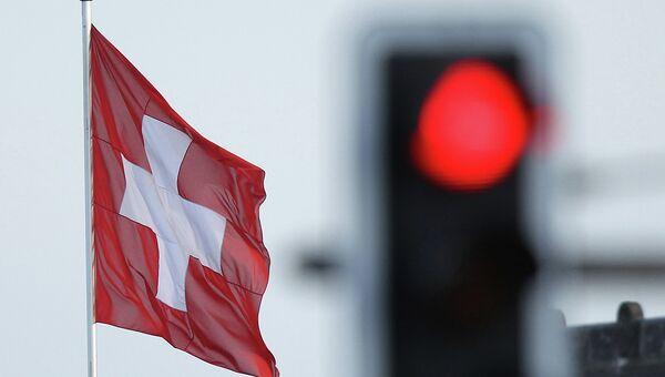 Флаг Швейцарии на фоне красного сигнала светофора. Архивное фото