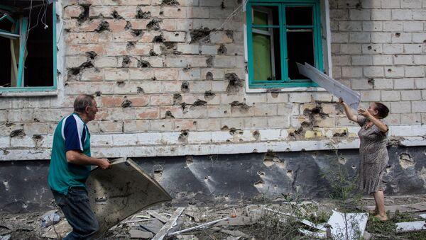 Местные жители после попадания мины во двор жилого дома во время боя в городе Шахтерск под Донецком. Архивное фото