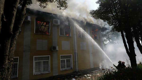 Украинские пожарные тушат огонь в разрушенном обстрелом здании в Донецке