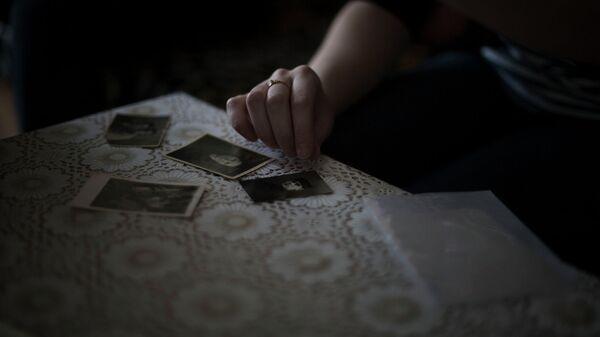 Крымская татарка показывает фотографии членов своей семьи, депортированной из Крыма