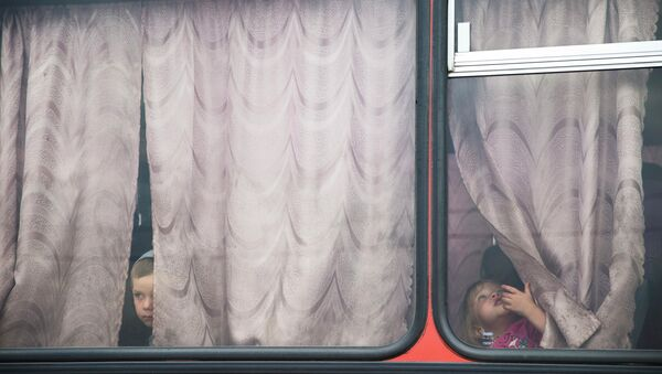 Дети в автобусе перед отъездом из лагеря для беженцев в Донецке Ростовской области. Архивное фото