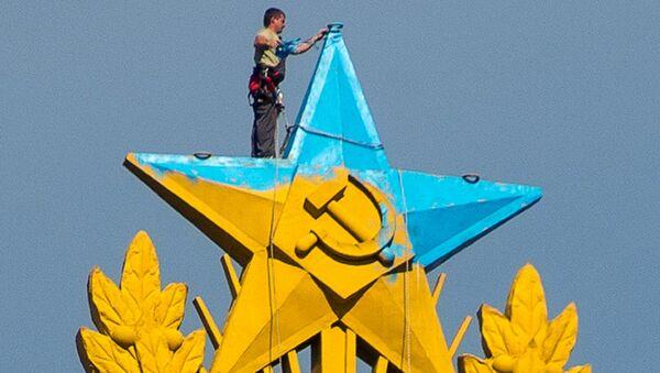 Рабочий закрашивает звезду на шпиле высотного здания на Котельнической набережной в Москве. Архивное фото