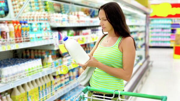 Женщина выбирает молочную продукцию в магазине. Архивное фото