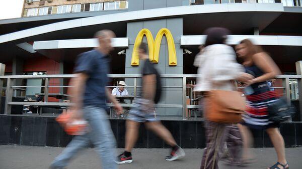 Люди проходят мимо ресторана быстрого питания Макдоналдс на улице Большая Бронная в Москве