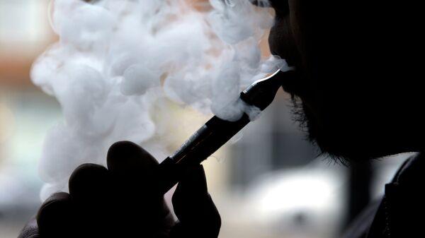 Мужчина курит электронную сигарету. архивное фото