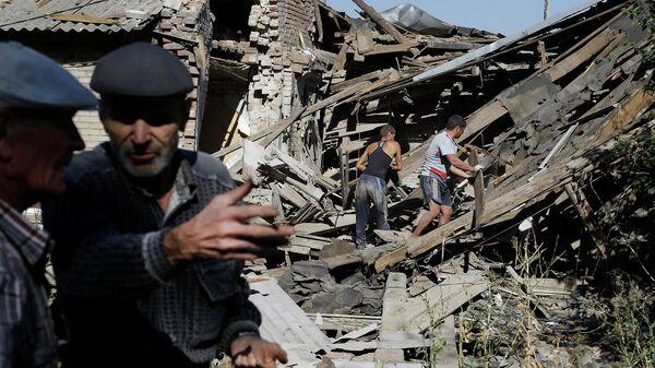 Местные жители разбирают завалы на месте жилого дома пострадавшего в результате боев под Иловайском. Архивное фото