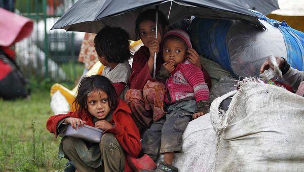 Дети прячутся от дождя во время наводнения в Индии, 6 сентября 2014