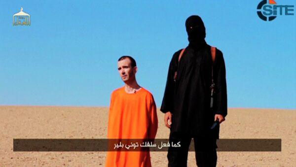 Кадр из видеозаписи, на которой боевики ИГ казнят гражданина Великобритании Дэвида Хэйнса