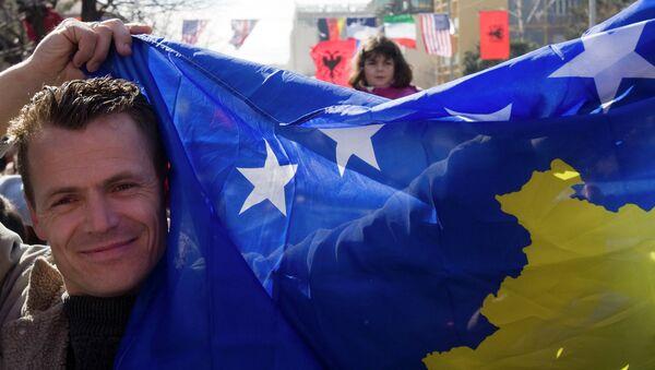 Мужчина с флагом Косово на улице в Приштине