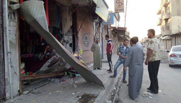 Жители города Рагга осматривают разрушенный магазин после авиаударов США по Сирии