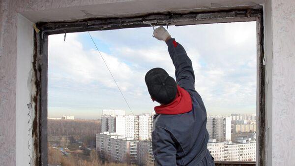 Рабочий устанавливает новые окна в квартире